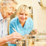 elderly and caregiver cooking